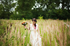 Young bride with bouquet of flowers in her hands Royalty Free Stock Photo