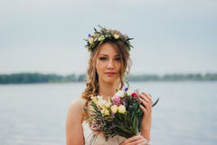 Young bride with a bouquet of flowers standing on the background the river Royalty Free Stock Photos