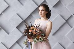 Young bride with bouquet horizontal portrait in studio. Gray geometric background royalty free stock photos
