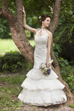 Young bride with bouquet near tree Stock Image