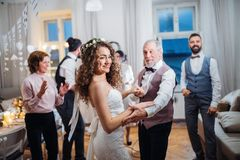 A young bride dancing with grandfather and other guests on a wedding reception. A young bride dancing with father or grandfather and other guests on a wedding stock photo