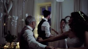 A young bride dancing with grandfather and other guests on a wedding reception. stock video
