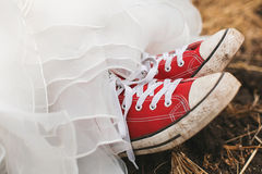 Young bride in dirty plimsolls on ground Royalty Free Stock Photo
