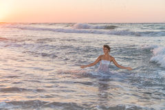 Young bride enjoys an accidental bath in the ocean waters. Royalty Free Stock Images