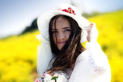 Young bride in a field. Portrait of a young woman in a wedding dress and a hat Royalty Free Stock Images