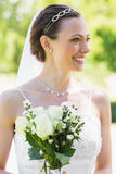 Young bride with flower bouquet in garden Royalty Free Stock Photos
