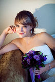 Young bride with flower on the sofa Royalty Free Stock Images