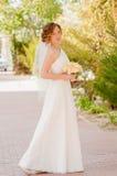 Young bride in a garden in a white dress Stock Photos