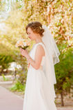 Young bride in a garden in a white dress Royalty Free Stock Photo