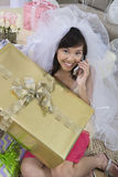 Young Bride With Gift Communicating On Mobile Phone Stock Photography