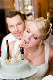 Young bride is going to bite her cake. With groom in background stock image