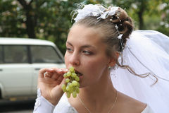 Young bride with grape. Young bride eating a grape Royalty Free Stock Photo