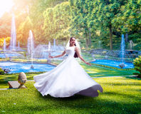 Young bride in green park with fountains Stock Photography