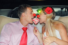 Bride and groom with clown noses sit in car. Young bride and groom with clown noses sit in car and lick one candy heart. Pink wedding royalty free stock images