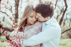 Young Bride and Groom couple in a blooming garden. Tender holding each other. Young family outdoor image near blooming. Apple tree. Love and tenderness Stock Photo