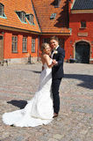 A Young Bride and Groom Dancing. A Young fair Bride and a dark Groom Dancing at a palace yard in bright sunshine. The castle is in terracotta colour Stock Photos