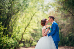 Young bride and groom embracing against the backdrop of the forest the road Royalty Free Stock Photography
