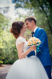 Young bride and groom embracing against the backdrop of the forest the road Stock Photography