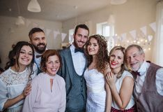 A young bride, groom and guests posing for a photograph on a wedding reception. A young bride, groom and other guests posing for a photograph on a wedding royalty free stock photos