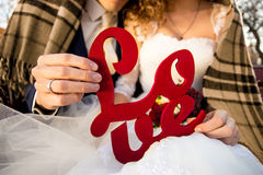 Young bride and groom holding Love sign in hands Stock Image