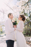 Young bride and groom hugging with bouquet of spring flowers near fence Royalty Free Stock Images