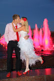 Bride and groom kiss near pink fountains Royalty Free Stock Image