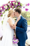 Young bride and groom kissing under arc at wedding ceremony Stock Photos