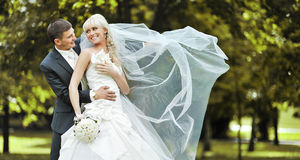 Young bride and groom laughing and looking to each other Stock Photography