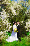 Young bride and groom in a lush garden in the spring Stock Photos
