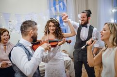 A young bride, groom and other guests dancing and singing on a wedding reception. A young cheerful bride, groom and other guests dancing, singing and playing royalty free stock images