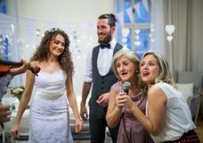 A young bride and groom with other guests dancing and singing on a wedding reception. A young cheerful bride and groom with other guests dancing and singing on royalty free stock photos