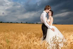 Young bride and groom posing in wheat field with dramatic sky in Royalty Free Stock Photos