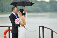 Young bride and groom in a rainy day Stock Images