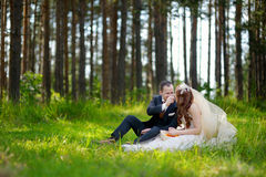 Young bride and groom sitting on a grass Stock Photo