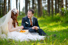 Young bride and groom sitting on a grass Royalty Free Stock Images
