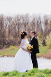 Young bride and groom in the spring of the river Royalty Free Stock Images