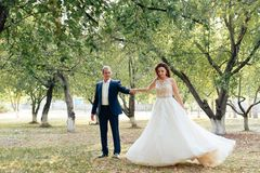 Young bride and groom walking in a summer Park with green trees. 1 stock photo