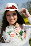 Young bride with hat and bouquet. Portrait of a young woman in a wedding dress holding a bouquet of flowers Royalty Free Stock Image