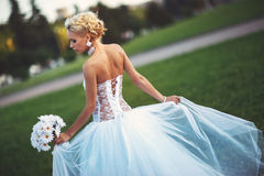 Young bride in her wedding dress and bouquet of flowers. Young beautiful bride in a white wedding dress and bouquet of daisies in her hand Royalty Free Stock Photo