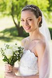 Young bride holding bouquet in garden. Portrait of young bride holding bouquet in garden Stock Images