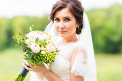 Young bride holding bouquet, portrait Royalty Free Stock Photo