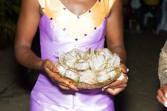 Young bride holding a bowl of wrapped candies royalty free stock image
