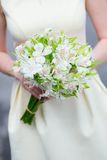 Young bride holding in her hands wedding flowers Stock Photo