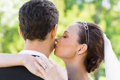 Young bride kissing groom on cheek Royalty Free Stock Photography