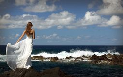 Young fiancee in light white wedding dress standing on windy sea roch shore on Sao Miguel island, Azores