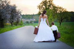 Young bride and little child on the road. With a suitcase, springtime Royalty Free Stock Image