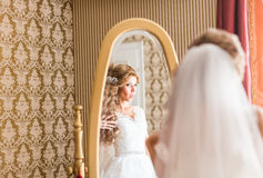 Young bride looks at herself in the mirror Royalty Free Stock Photography
