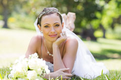 Young bride lying on grass in park Stock Photography