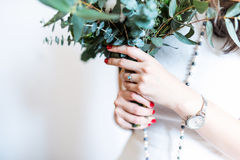 Young bride with modern bouquet. Closeup of hand with engagement ring and perfect manicure stock photography