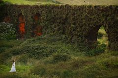 Young bride near grassy brickwall in green landscape of Sao Miguel Island stock photo